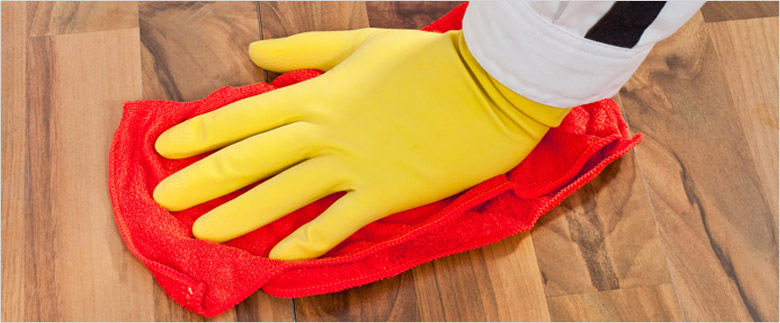 Cleaning the wooden floor with a red washcloth